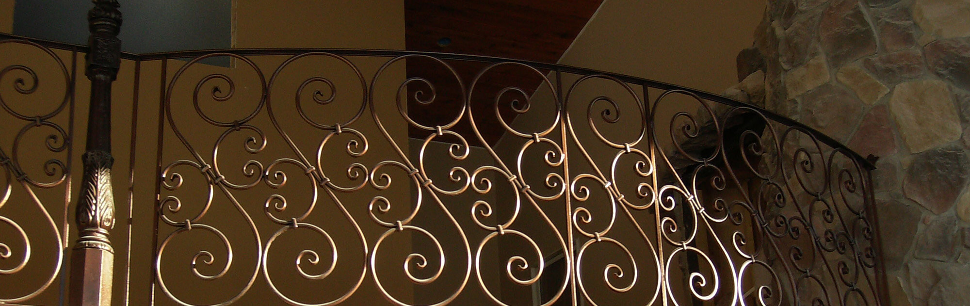 Custom wrought iron balcony railing featuring scroll balusters in a copper powder coated finish